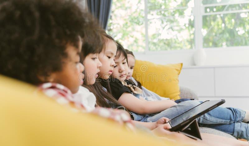 Gruppo di piccoli bambini che guardano insieme il fumetto di film del film sulla compressa digitale Bambini che giocano con la co fotografia stock