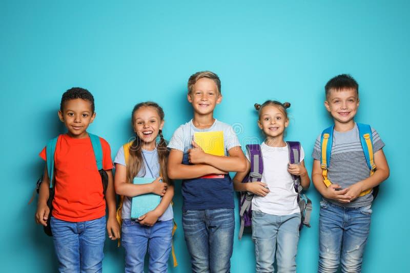 Gruppo di piccoli bambini con i rifornimenti di scuola degli zainhi sul fondo di colore fotografie stock libere da diritti