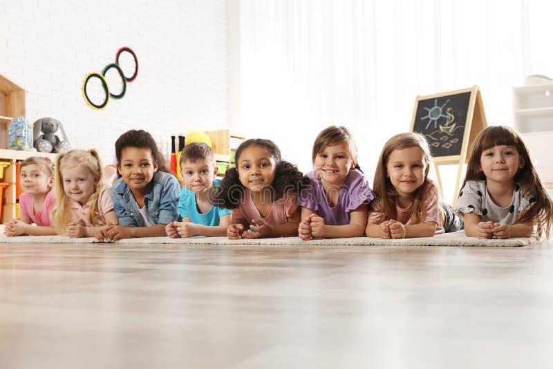 Gruppo di piccoli bambini svegli che si trovano sul pavimento Attivit? di ricreazione di asilo immagini stock libere da diritti