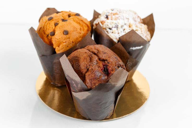 Gruppo di primo piano del dolce della tazza del muffin Con di pepita di cioccolato ed il materiale da otturazione della frutta immagini stock