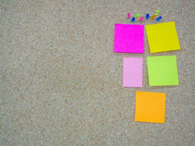 Gruppo di puntine da disegno appuntate e nota di carta sul bordo del sughero immagine stock libera da diritti