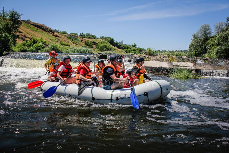 Gruppo di rafting, sport acquatico di estremo di estate Gruppo di avventuriere che fa rafting dell'acqua bianca immagine stock
