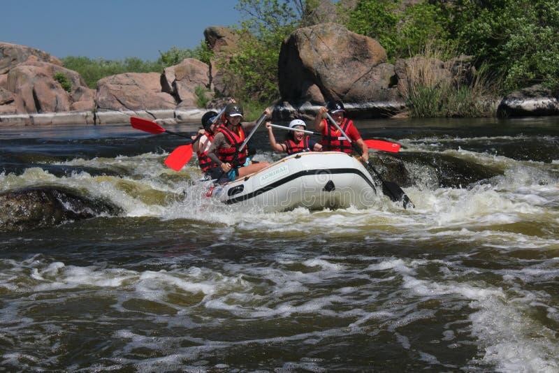 Gruppo di rafting, sport acquatico di estremo di estate Gruppo di avventuriere che fa rafting dell'acqua bianca immagini stock