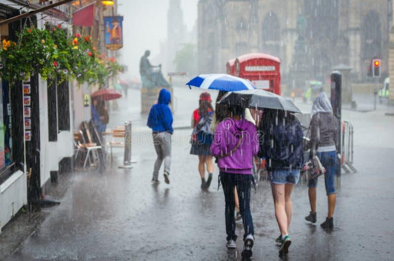 Gruppo di ragazze che camminano alla pioggia di estate nella città fotografia stock libera da diritti