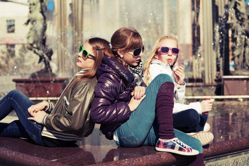 Gruppo di ragazze teenager accanto alla fontana della città fotografia stock