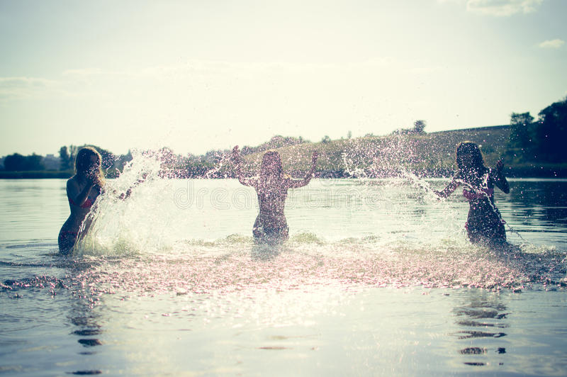 Gruppo di ragazze teenager felici che giocano in acqua immagine stock