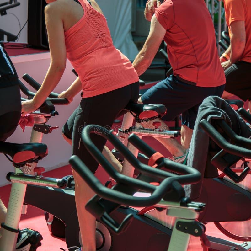 Gruppo di ragazzi e di ragazze alla palestra: Allenamento con le bici di filatura fotografia stock