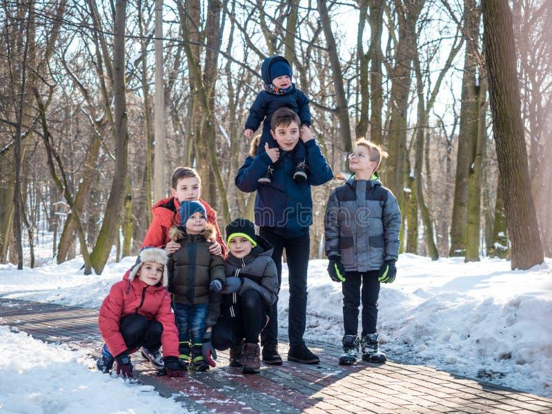 Gruppo di ragazzini che posano per la macchina fotografica nel parco di inverno fotografie stock