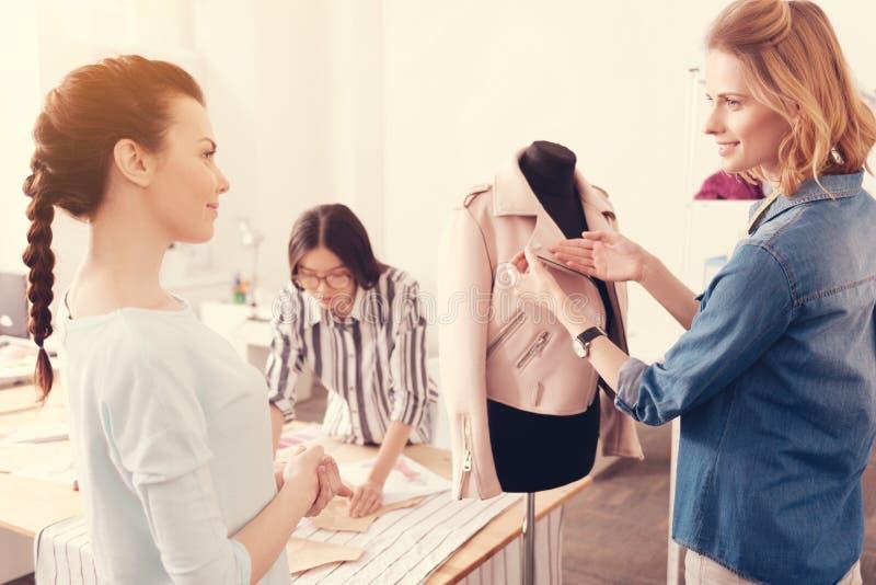 Gruppo di riusciti progettisti che discutono la nuova raccolta dei vestiti fotografia stock