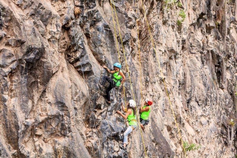 Gruppo di scalatori coraggiosi che scalano una parete della roccia fotografia stock