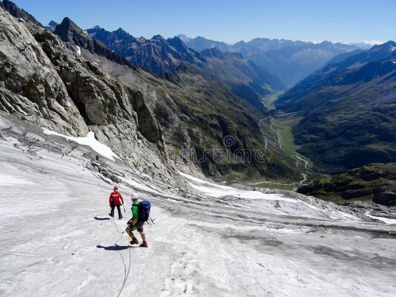 Gruppo di scalatori di montagna maschii che attraversano un ghiacciaio sulla loro direzione giù da un alto picco alpino fotografie stock libere da diritti