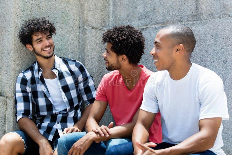 Gruppo di scherzare l'uomo afroamericano e caucasico dei pantaloni a vita bassa fotografia stock libera da diritti
