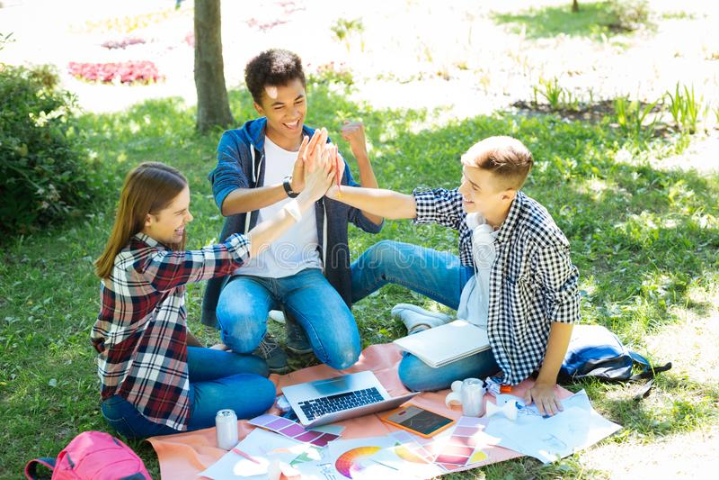 Gruppo di sogno degli studenti d'orientamento che ritengono insieme felici fotografie stock