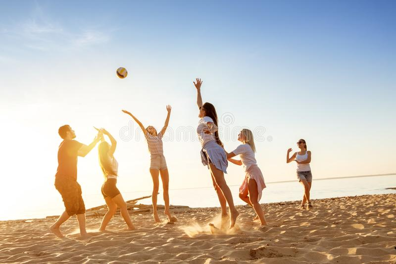 Gruppo di spiaggia di tramonto della palla dei giochi degli amici fotografie stock libere da diritti