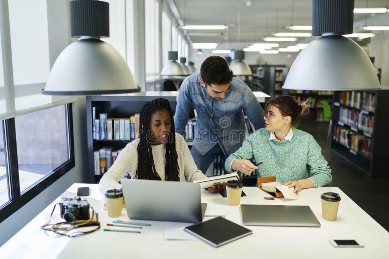 Gruppo di studente che prepara per gli esami nella biblioteca di univercity immagini stock
