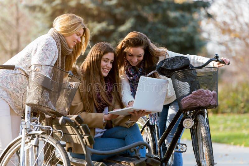 Gruppo di studentesse di college sorridenti sul banco di parco che lavora al computer portatile fotografia stock libera da diritti