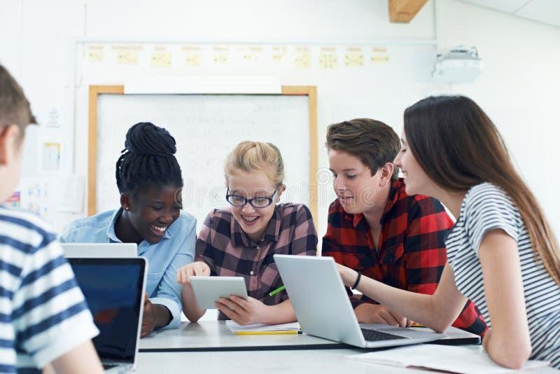 Gruppo di studenti adolescenti che collaborano sul progetto nella classe dell'IT fotografia stock