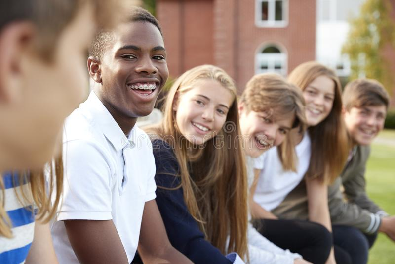 Gruppo di studenti adolescenti che si siedono fuori degli edifici scolastici immagine stock