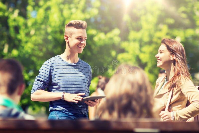 Gruppo di studenti adolescenti con i outoors del pc della compressa fotografia stock
