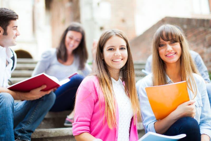 Gruppo di studenti che si siedono all'aperto immagine stock