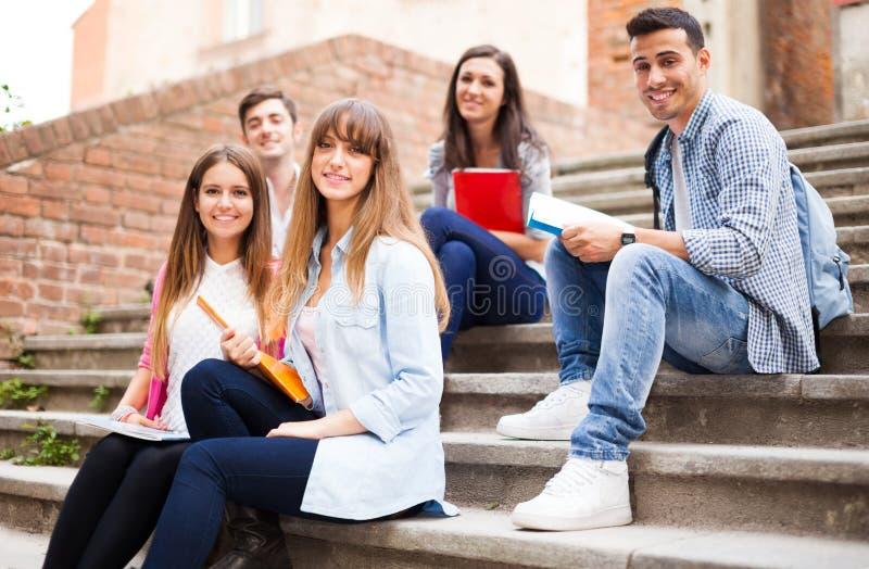 Gruppo di studenti che si siedono all'aperto immagini stock libere da diritti