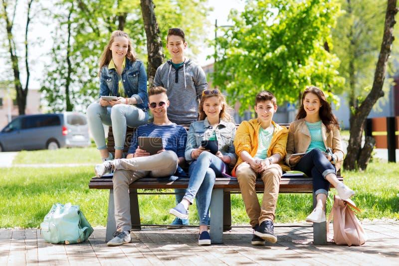 Gruppo di studenti con il pc della compressa al cortile della scuola immagini stock libere da diritti