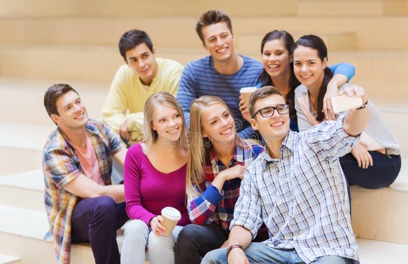 Gruppo di studenti con la tazza di caffè e dello smartphone fotografia stock