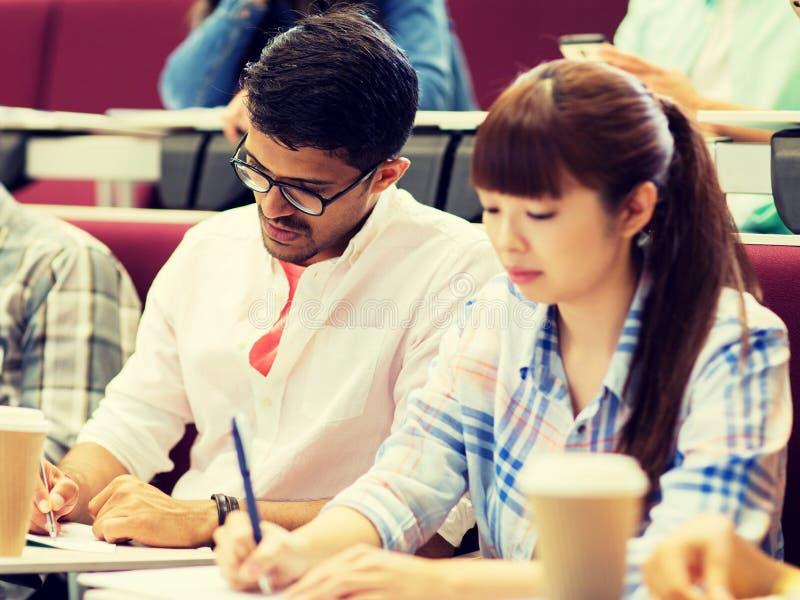 Gruppo di studenti con scrittura del caffè sulla conferenza fotografie stock libere da diritti