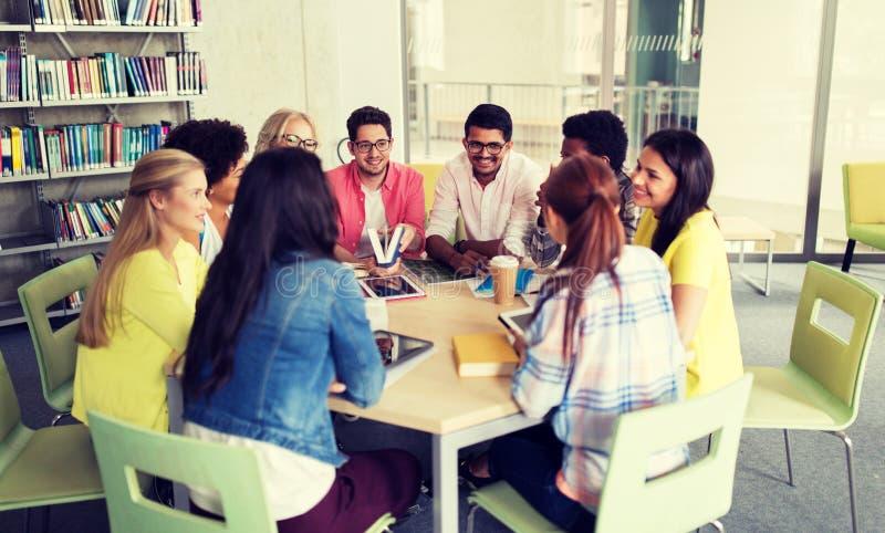 Gruppo di studenti della High School che si siedono alla tavola immagini stock