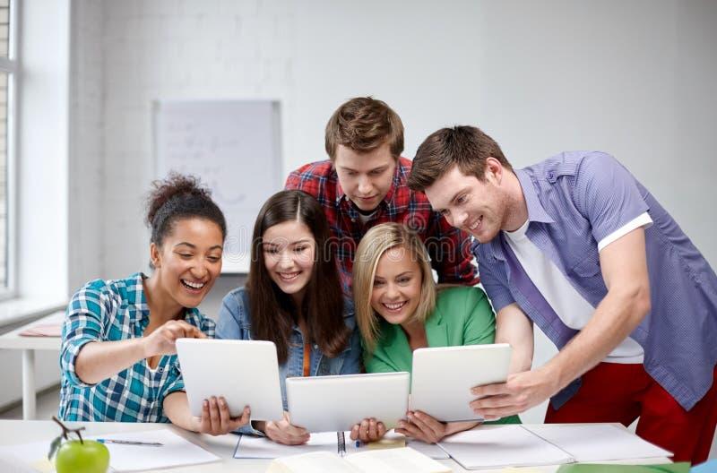Gruppo di studenti felici della High School con il pc della compressa fotografia stock libera da diritti