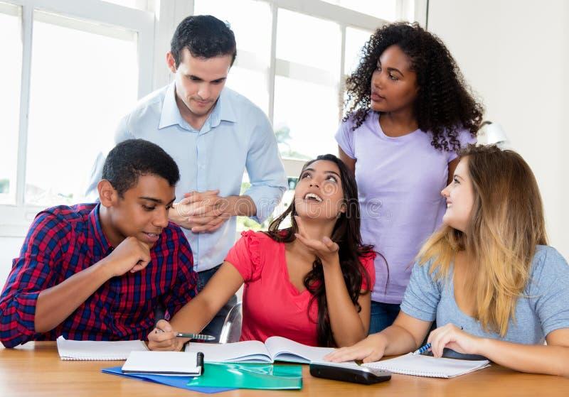 Gruppo di studenti internazionali con l'insegnante che prepara per l'esame fotografia stock
