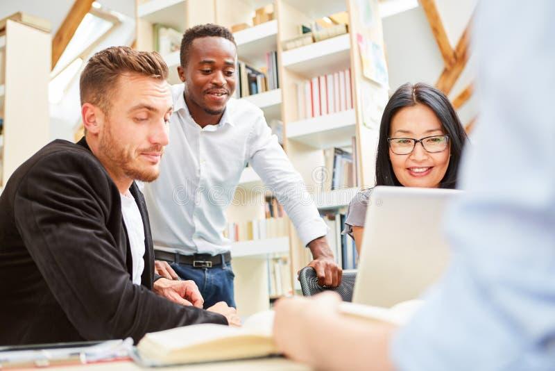 Gruppo di studenti nella biblioteca mentre imparando immagine stock libera da diritti
