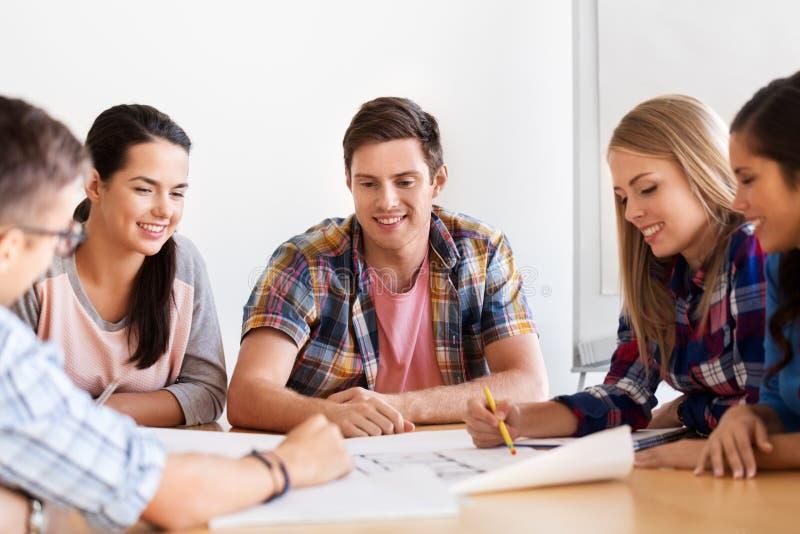 Gruppo di studenti sorridenti con il modello immagine stock