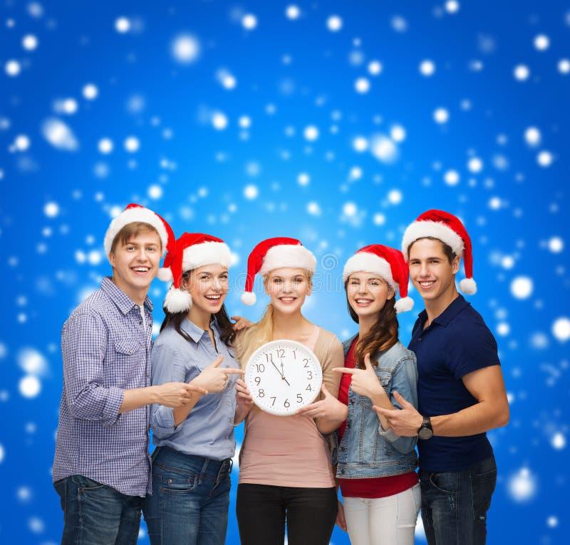 Gruppo di studenti sorridenti con l'orologio che mostra 12 immagine stock libera da diritti