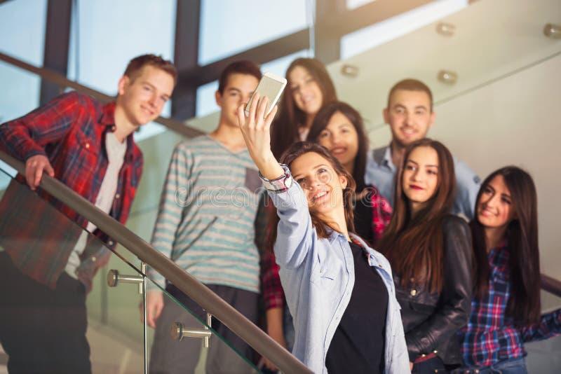 Gruppo di studenti sorridenti con lo smartphone che prende selfie immagini stock