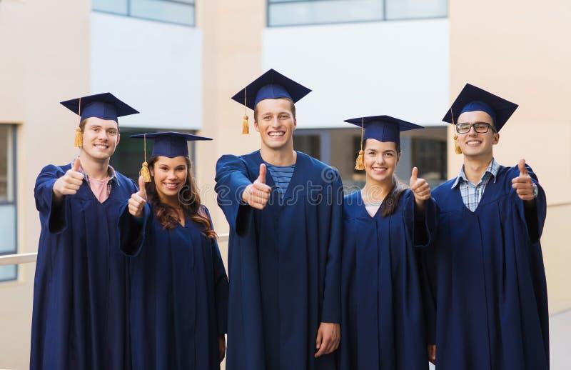 Gruppo di studenti sorridenti in tocchi immagini stock