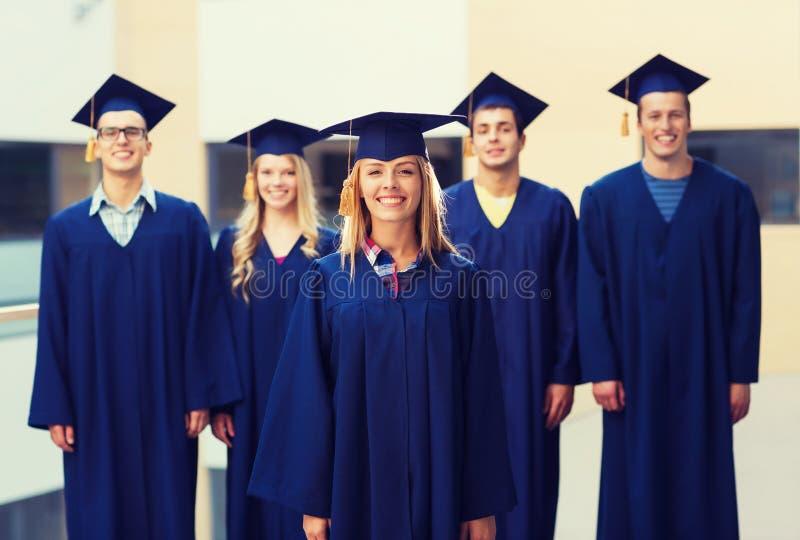 Gruppo di studenti sorridenti in tocchi immagine stock libera da diritti