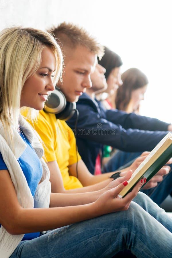 Gruppo di studenti sui libri di lettura della rottura e sugli smartphones usando fotografia stock libera da diritti