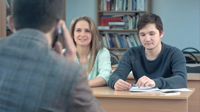Gruppo di studenti universitari che si siedono ai loro scrittori in sala ed in insegnante aspettante, mentre lui che parla sopra fotografia stock libera da diritti
