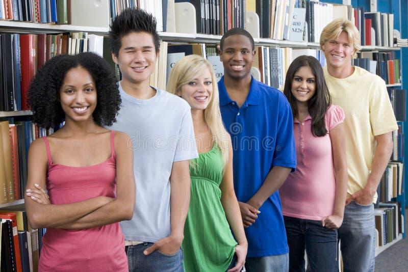 Gruppo di studenti universitari in libreria fotografia stock