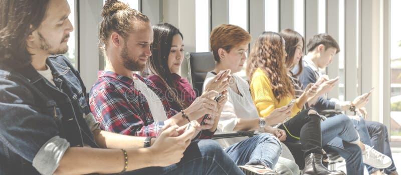Gruppo di gruppo di tecnologia che si siede e che per mezzo dell'aggeggio digitale dello smartphone Il gruppo di gruppo creativo  immagini stock