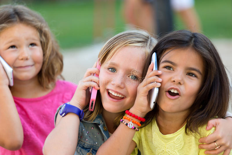 Gruppo di telefoni cellulari usando dei bambini nel parco fotografie stock