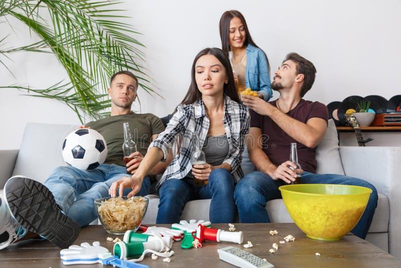Gruppo di tifosi degli amici che guarda gli alimenti industriali della partita di calcio immagine stock