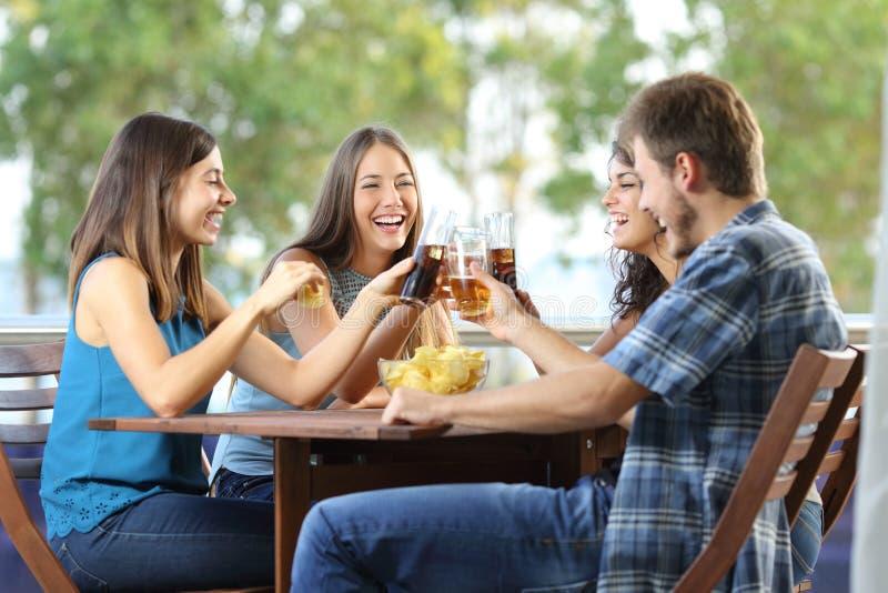Gruppo di tostatura felice degli amici fotografia stock