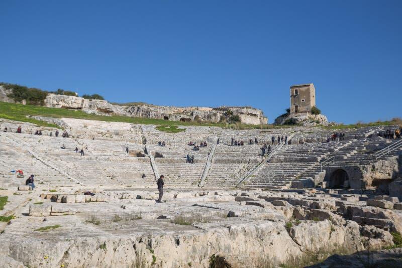 Gruppo di turisti che visitano il teatro greco a Siracusa, Sicilia, Italia fotografia stock libera da diritti