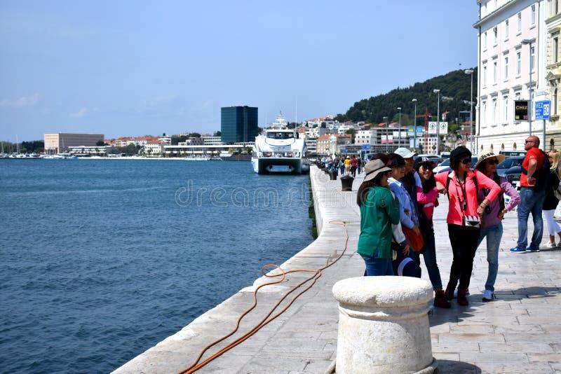 Gruppo di turisti felici che posano per una foto alla spaccatura, Croazia, il 22 aprile 2019 fotografia stock libera da diritti