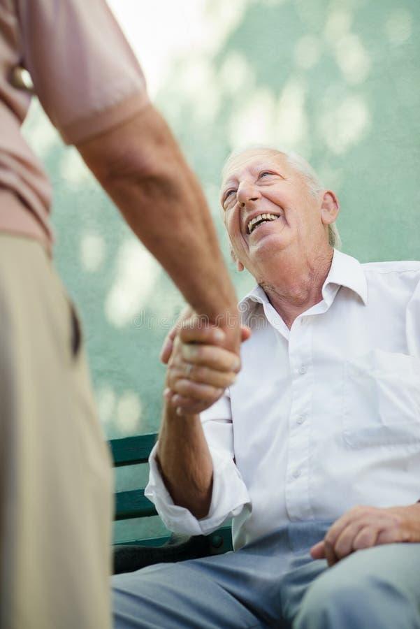 Gruppo di uomini anziani felici che ridono e che comunicano immagini stock