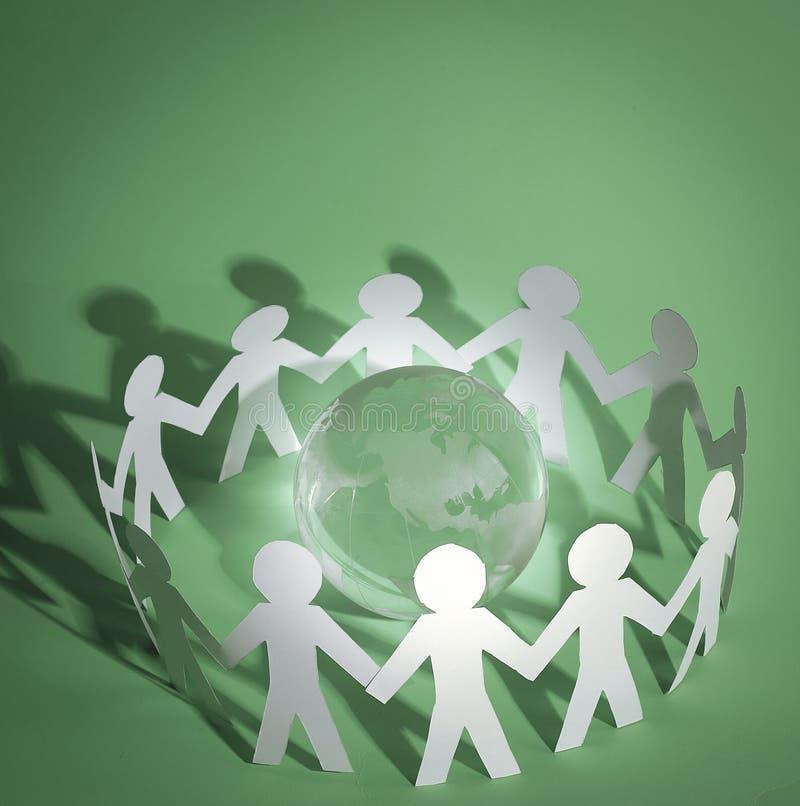 Gruppo di uomini di carta che stanno intorno al globo di vetro royalty illustrazione gratis