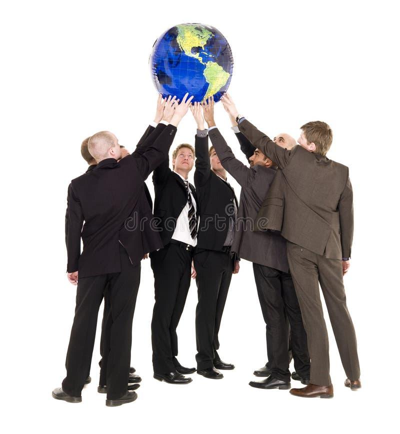 Gruppo di uomini che tengono un globo terrestre fotografia stock libera da diritti