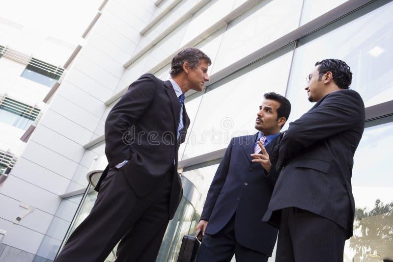 Gruppo di uomini d'affari che comunicano fuori del buildi dell'ufficio immagini stock